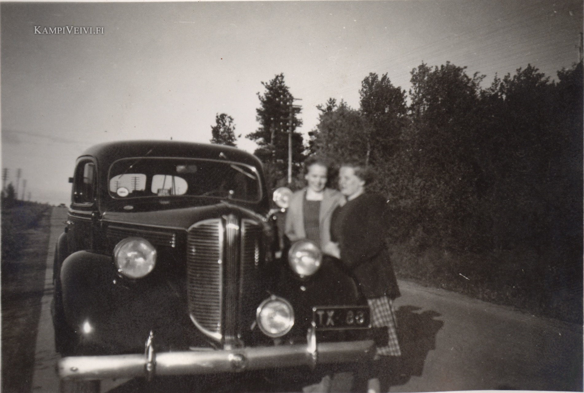 Evi ja hänen ystävänsä auton vierellä